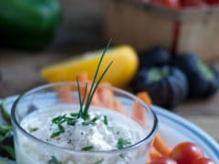 Shrimp Crab Dip for Crudités - Dairy Free - Dip in small, clear glass bowl, garnished with chives on a platter with slice yellow peppers, celery, carrots and cherry tomatoes