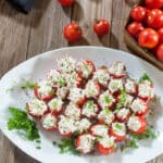 Chicken Stuffed Tomato Bites Appetizers- Platter filled with cherry tomatoes stuffed with chicken salad garnished with snipped celery tops