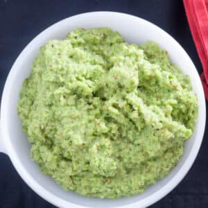 Bright green Garlic Scape Pesto with chunks of almonds in white bowl on black background