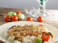 Roasted Garlic Rosemary Salmon on a bed of jasmine rice with roasted halved brussels sprouts and halved fresh cherry tomatoes
