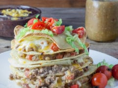 Large stack of tortillas with meat and cheese between each layer topping with shrdded lettuce and diced cherry tomatoes