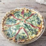Whole quiche in a pie tin with strips of roasted red peppers and lots of spinach