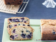 3 cut slices quick bread dotted with whole blueberries on green rectangular plate next to the whole quick bread