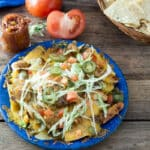 Chicken nachos with tomato salsa on blue plate