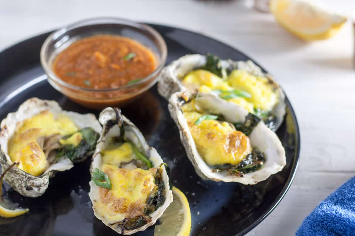 4 oysters rockefeller on black plate with bowl of hot saude