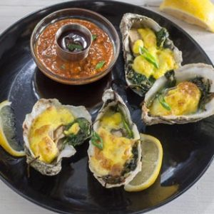 oysters rockefeller on black plate with spicy sauce in bowl