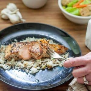 salmon with garlic butter on fork held by woman's hand