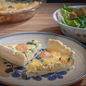 shrimp and asparagus quiche on beige plate with blue markings