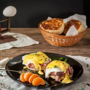 eggs benedict on black plate with clementine garnish