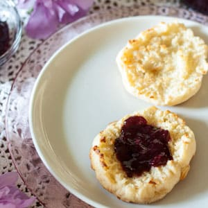 Blackberry jam on English Muffin on white plate