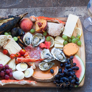 cheese, fruit and meat on bamboo board