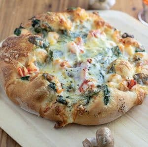 crispy, browned lobster pizza on wooden peel