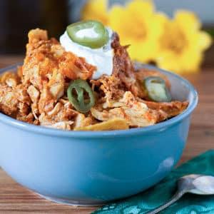 crockpot enchilada casserole in blue bowl garnished with sour cream and jalapenos