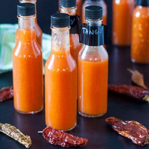bottles of fermented hot sauce on black board