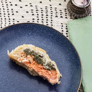 slice of salmon wellington on blue plate