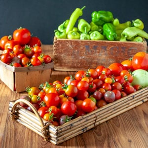 colorful tomatoes and peppers in baskets
