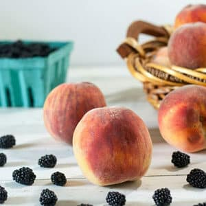 large peaches and blackberries on white board