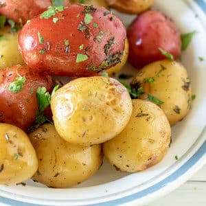 foil packet grilled potatoes in white bowl with blue rim.