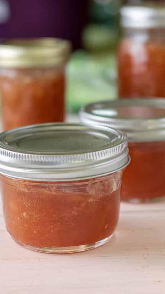 Jars on rhubarb jam on white board.