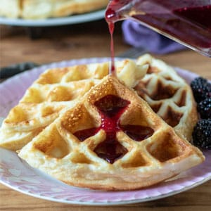 3 waffles on pink plate with blackberry syrup pouring