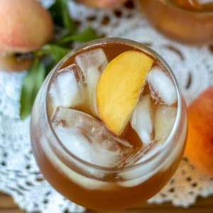 peach sun tea in glass with ice and garnished with peach slice.