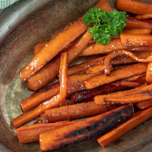 Browned glazed carrots in silver serving dish.