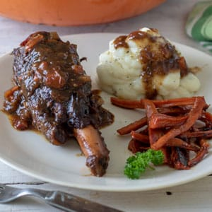 Venison shank on white plate with gravy, potatoes and carrots