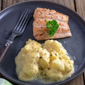 Creamy cauliflower au grating on gray plate with salmon filet.