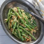 Green beans and almonds, toasted, in silver platter.