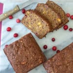 Orange cranberry pumpkin quick bread slices on marble board.