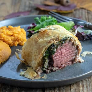 Slice of venison wellington on gray plate