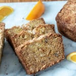 Orange pineapple quick bread sliced on marble board.