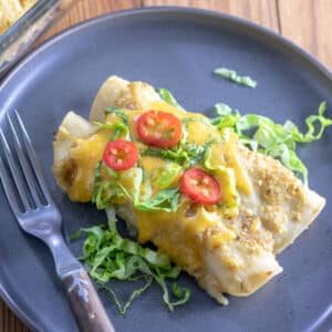 Turkey enchiladas verdes on gray plate with colorful garnishes