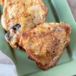 Crispy chicken thighs on green plate.