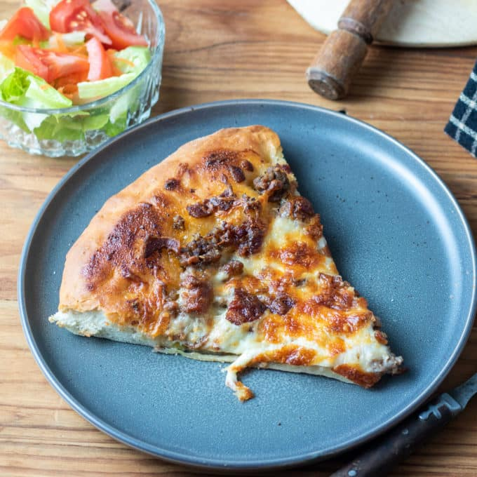 slice of cheeseburger pizza on grey plate.