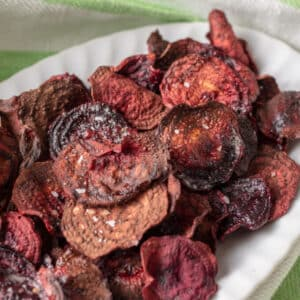 Colorful beet chips on white plate.