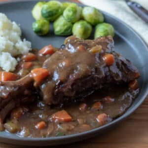 lamb shank with gravy on gray plate