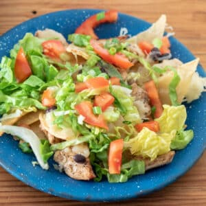 Chicken nachos on blue pewter plate topped with lettuce and tomatoes.