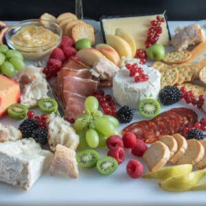 Grazing platter with cheese, sliced meats and colorful fruits.