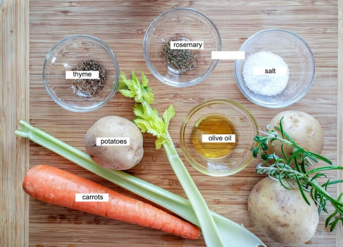 ingredients for pot roast- thyme, rosemary, salt, potatoes, olive oil, potatoes, sage, celery and carrots.