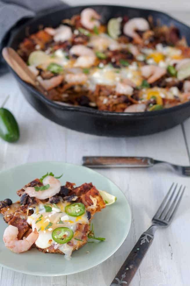 chilaquiles in cast pan with egg topped portion on plate
