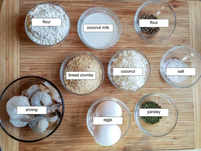 Ingredients for shrimp. Flour, coconut milk, pepper, salt, coconut, bread crumbs, egg, parsley, shrimp.