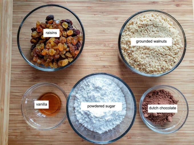 Ingredients for filling on wooden board- raisins, walnuts, vanilla powdered sugar, dutch chocolate.