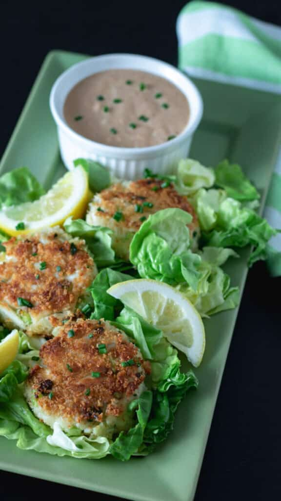 Crab cakes on green platter.