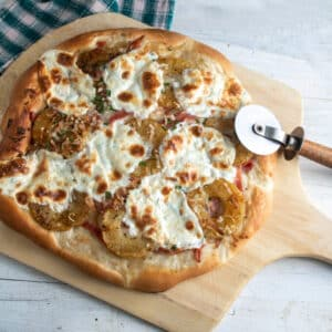 Ham pineapple pizza on wooden pizza peel.