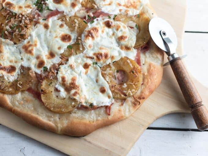 Tasted coconut, pineapple, ham and mozzarella on pizza on wooden peel.