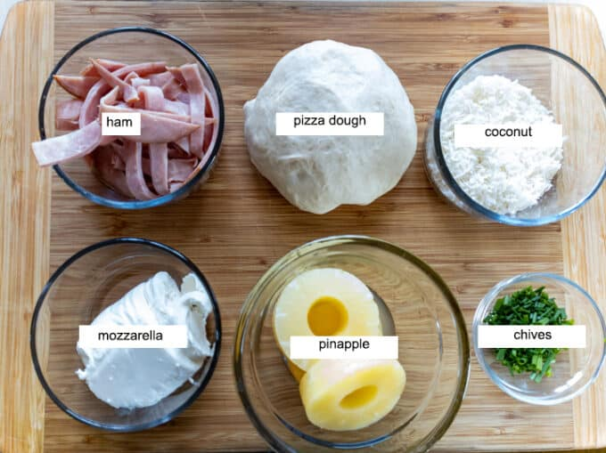 Ingredients for pizza- pizza dough, ham, coconut, mozzarella, pineapple, chives.