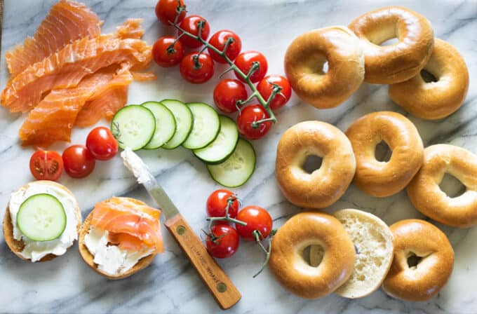 Bagel and lox appetizer spread on marble board.