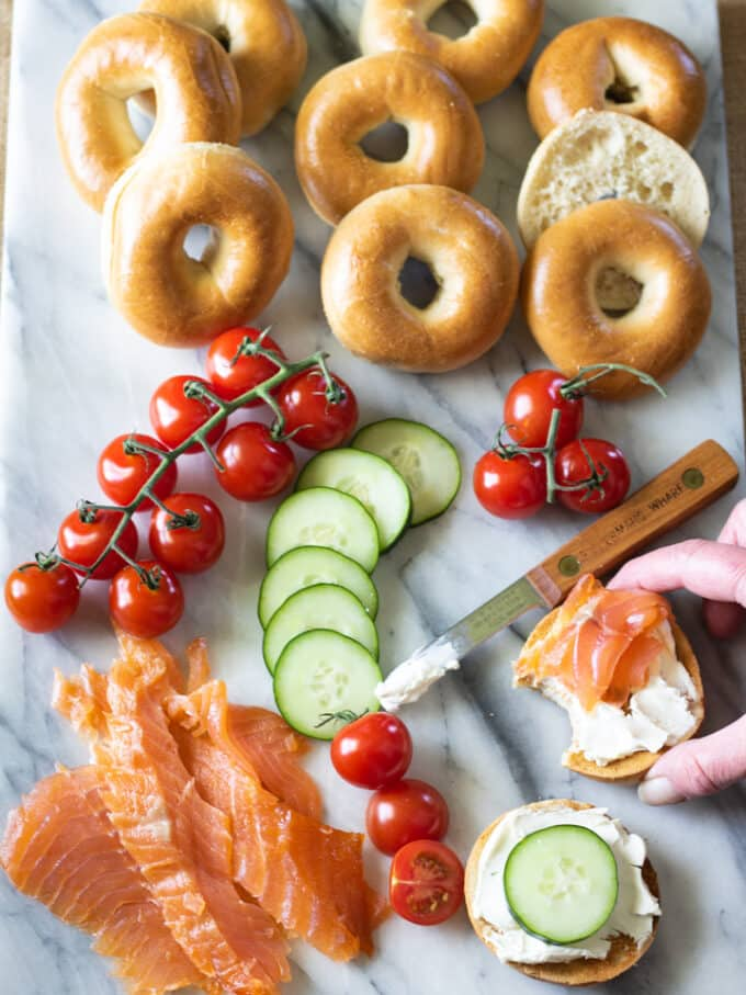 Hand grabbing bagel with lox. Sliced salmon on marble board with tomatoes, cucumbers and bagels.