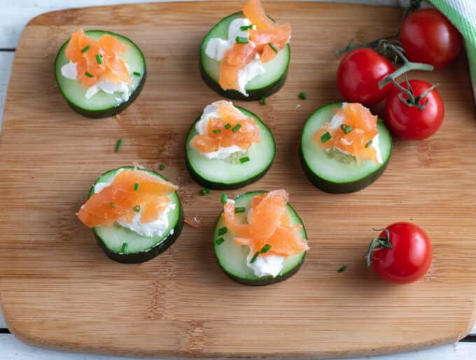 Cucumber and salmon appetizers on wooden board.